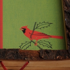 """Vibrant red cardinal in lower right corner """"pops"""" in the live-edge cherry """"frame""""."""