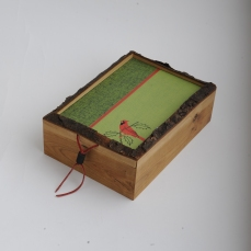 Box is live-edge cherry with pull handle of leather and milk-painted wooden bead.