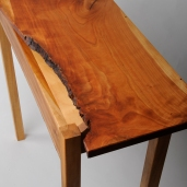 Jagged, dramatic live-edge with cutaway reveals maple legs and shelf.