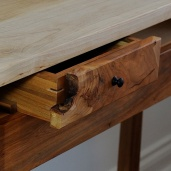 The natural curve of the burl on the drawer front reveals the spline joinery on the drawer.