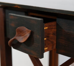 Drawer with hand-carved leaf handle.