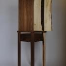 The smaller door is inset to sit behind the wider door. Sides feature book matched walnut veneer.